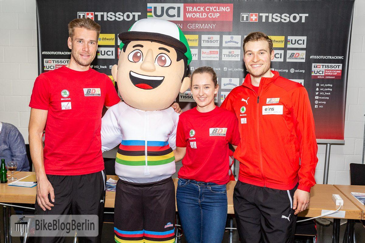 Foto zur Pressekonferenz des Bahn-Weltcups 2018, bei der das Maskottchen der WM vorgestellt wurde. Auf dem Foto sind drei Radsportler (Roger Kluge, Lea Lin Teutenberg und Stefan Bötticher) zu sehen, in ihrer Mitte das Maskottchen, ein Radfahrer mit WM-Trikot.
