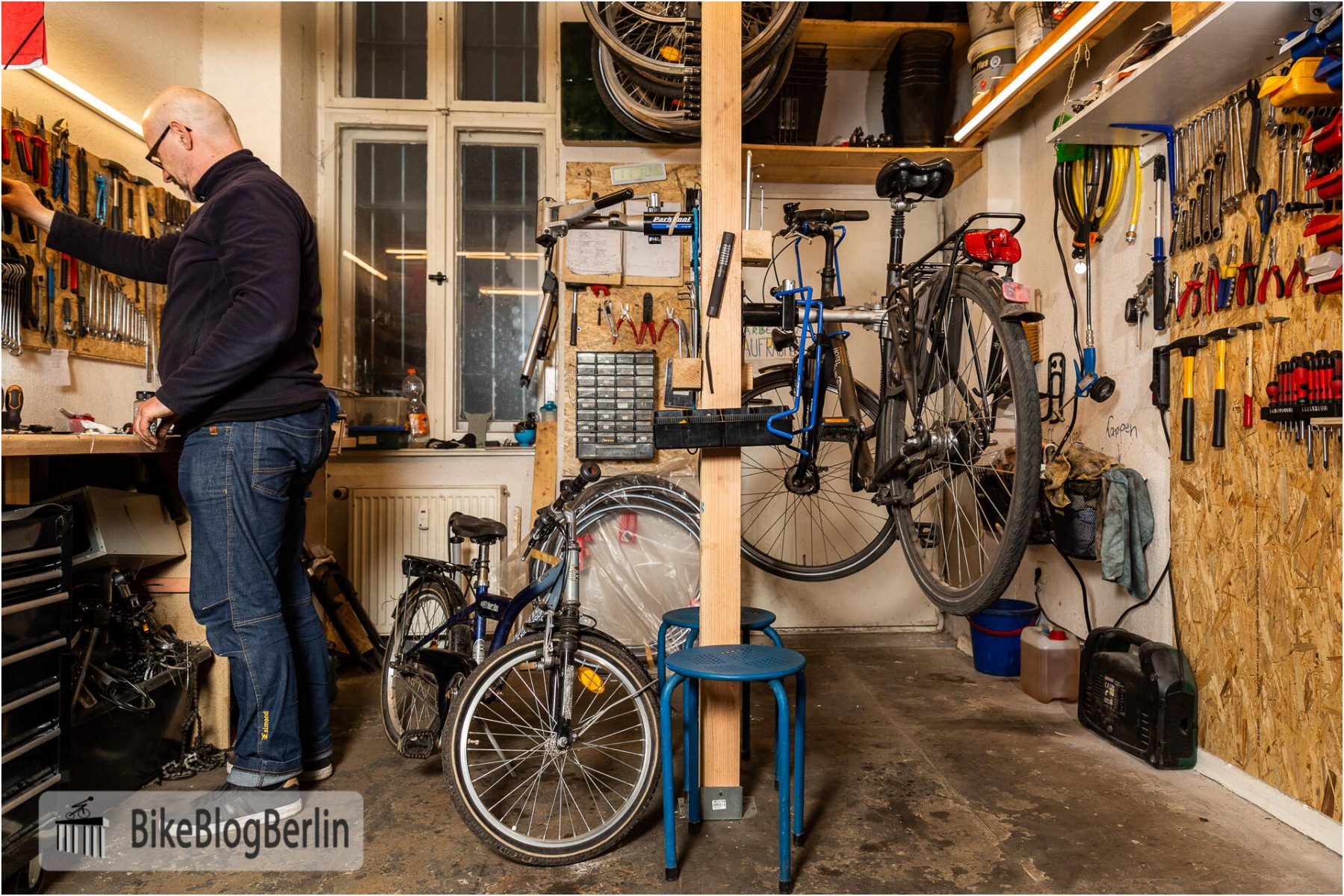 Die Werkstatt von Berlin Bike Tour. Sven steht an einer Werkbank an der linken Seite. In der Mitte ein Montageständer, auf der rechten Seite wartet ein Fahrrad auf die Reparatur.