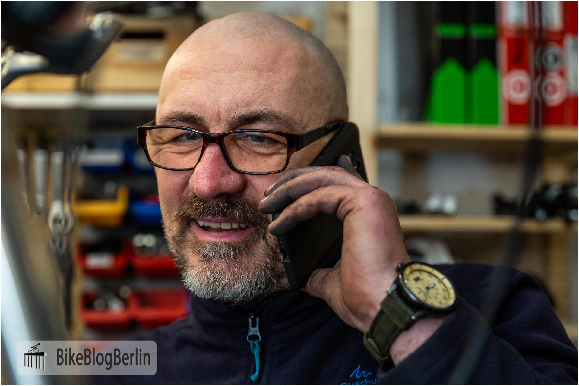 Sven Marx in der Werkstatt telefoniert mit einem Smartphone.