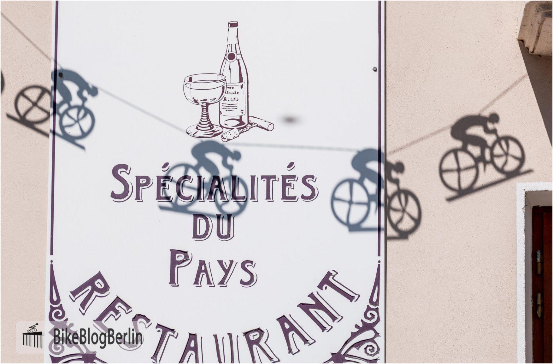 """Ein Restaurantschild in Frankreich: """"Spécialtités du Pays"""". Der Schatten einer Girlande fällt auf das Schild: es handelt sich um stilisierte Rennradfahrer."""