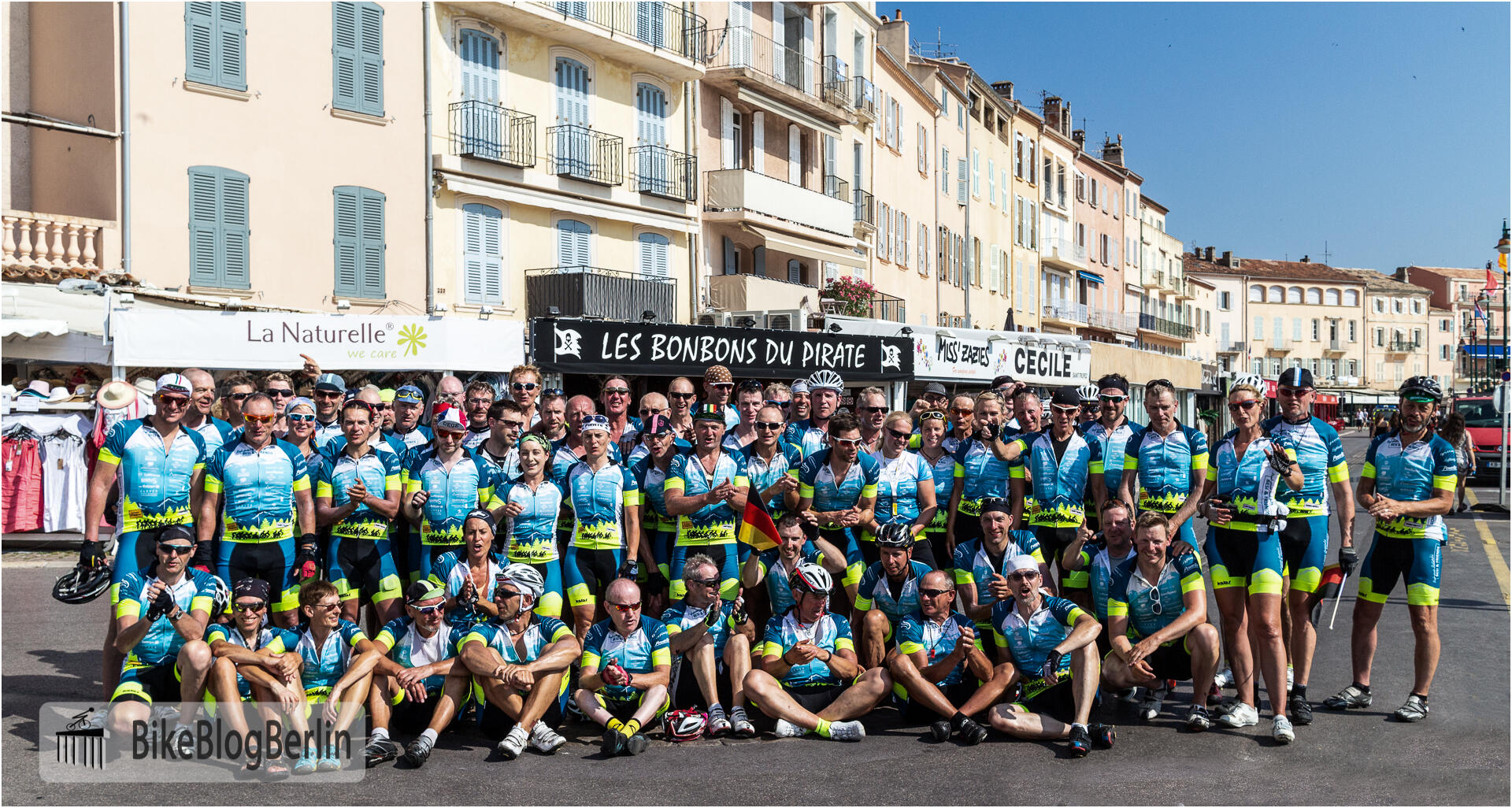 Das gesamte Team aufgereiht auf der Hafenpromenade von Saint-Tropez. Ein Teil des Teams sitzt auf dem Asphalt, die meisten stehen dahinter.