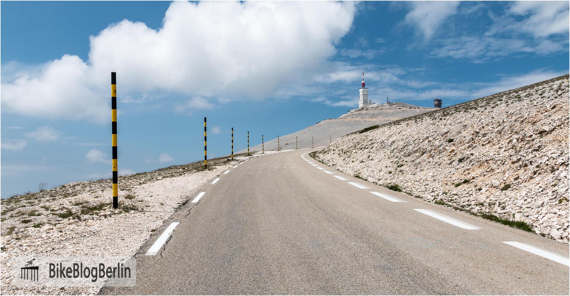 Die Straße zum Gipfel des Mont Ventoux. Links der Straße sind auffällig gemusterte Stangen zu sehen, die auch bei hohem Schnee die Straße begrenzen. Im Hintergrund der Gipfel.