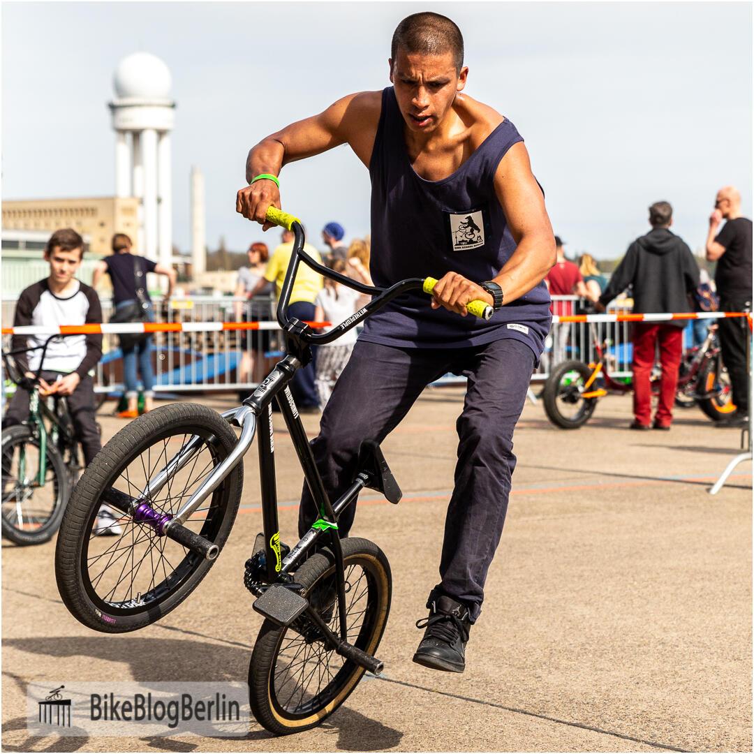 """BMX-Profi Camilio Gutierrez zeigt auf der VELOBerlin 2018 einen Trick auf dem BMX-Rad: er steht mit einem Fuß auf der Achsverlängerung (""""Peg""""), währen das Vorderrad in der Luft ist."""